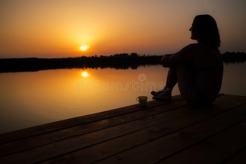 Vrouw het drinken koffie en het genieten van van zonsondergang op het houten dok stock foto's
