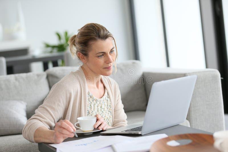 Vrouw het drinken koffie op middelbare leeftijd en thuis het werken stock fotografie