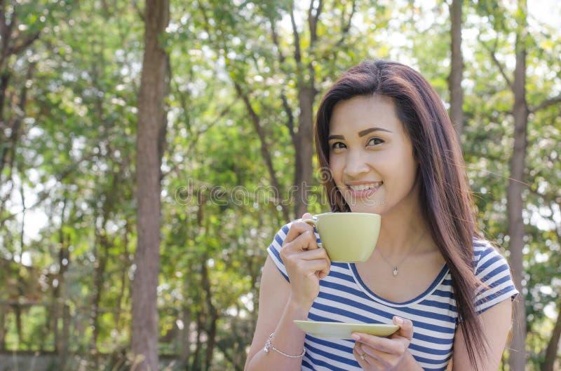 Vrouw het drinken koffie in park stock foto