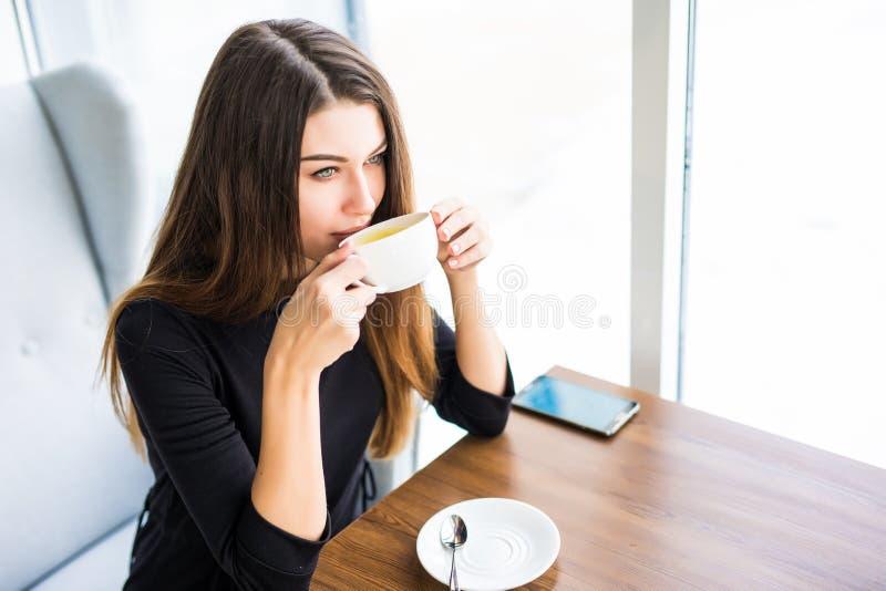 Vrouw het drinken koffie of thee in de ochtend bij restaurant Close-upportret van het mooie meisje met kop thee stock afbeelding