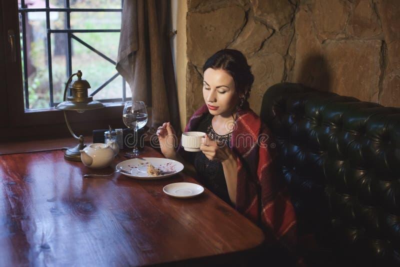Vrouw het drinken thee in een koffie in de avond royalty-vrije stock fotografie