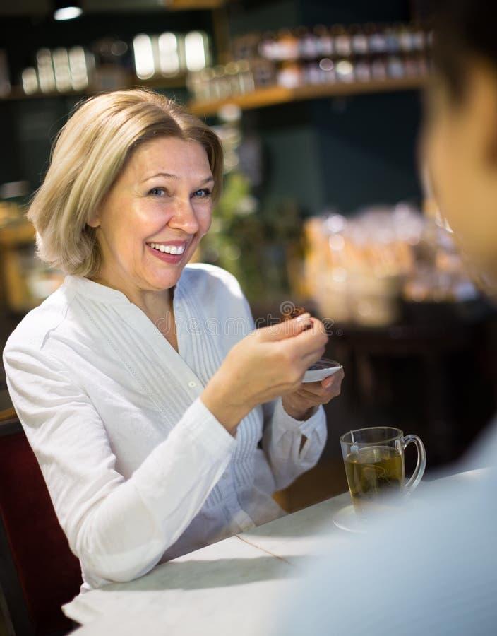 Vrouw het drinken thee en het spreken in coffee-house stock foto