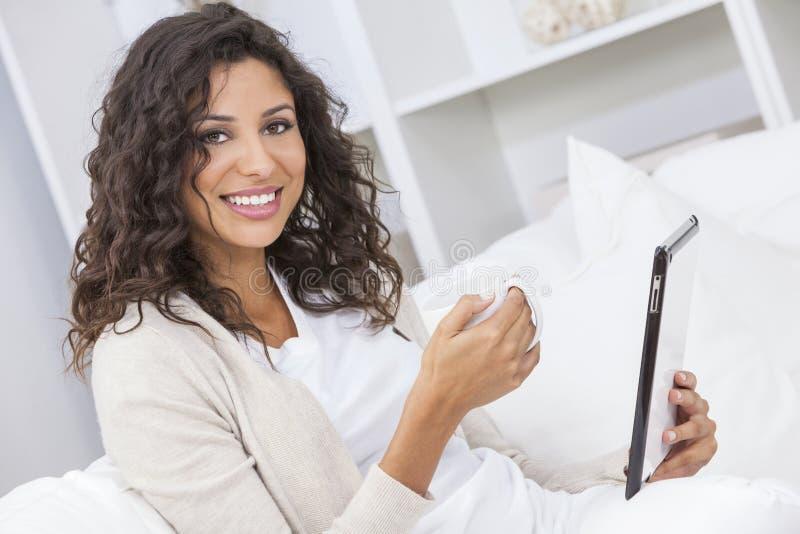 Vrouw het Drinken Thee of Koffie die Tabletcomputer met behulp van stock foto