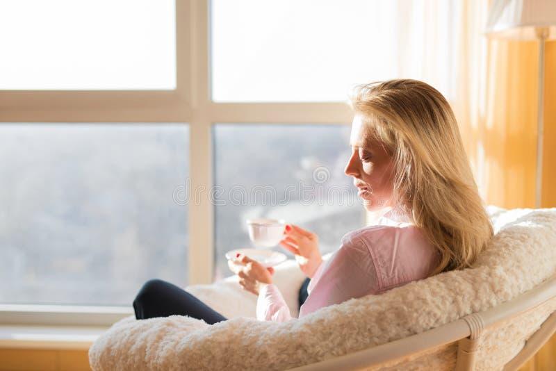 Vrouw het drinken thee terwijl thuis het ontspannen stock afbeeldingen