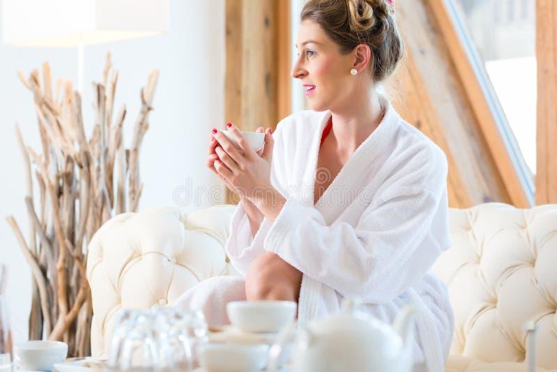 Vrouw het drinken thee in wellness spa stock foto