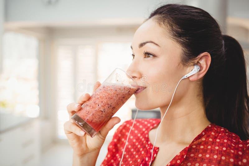 Vrouw het drinken vruchtensap terwijl het luisteren aan muziek stock foto