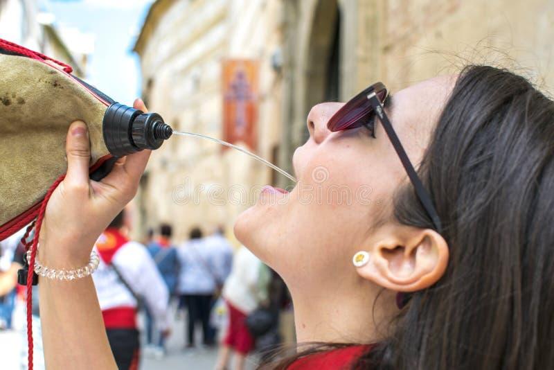 Vrouw het drinken wijn op een traditionele manier bij caballos Del Vino in Caravaca DE La Cruz, Spanje op 2 Mei 2019 stock foto