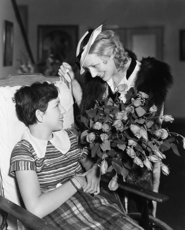 Vrouw het geven bloeit aan meisje in rolstoel (Alle afgeschilderde personen leven niet langer en geen landgoed bestaat Leverancie royalty-vrije stock foto's