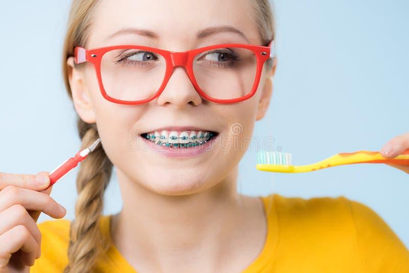Vrouw het glimlachen schoonmakende tanden met steunen stock foto