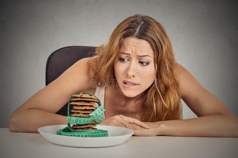 Vrouw het hunkeren naar suiker zoete koekjes maar ongerust gemaakt over gewichtsaanwinst royalty-vrije stock afbeelding