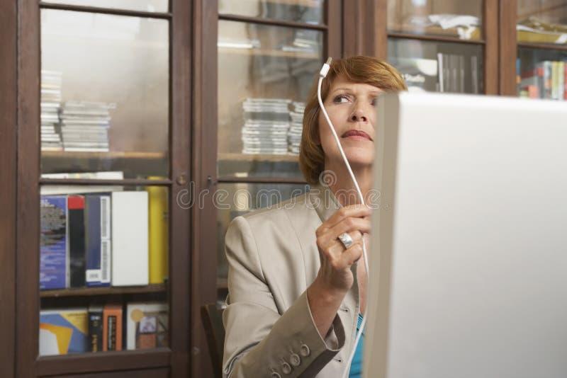 Vrouw het Inspecteren Computerkabel royalty-vrije stock afbeeldingen