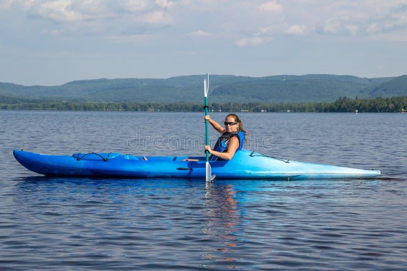 Vrouw het kayaking op een kalm meer stock fotografie