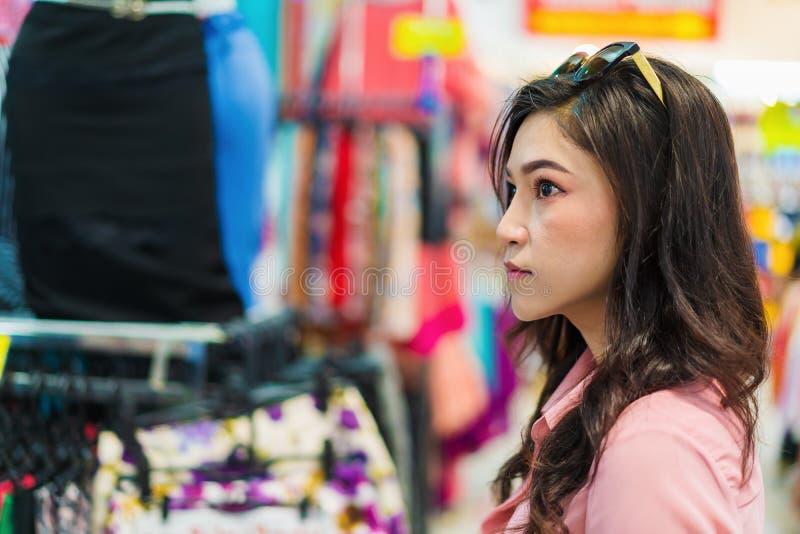 Vrouw het kiezen en het kopen kleren in het winkelen opslag stock afbeelding