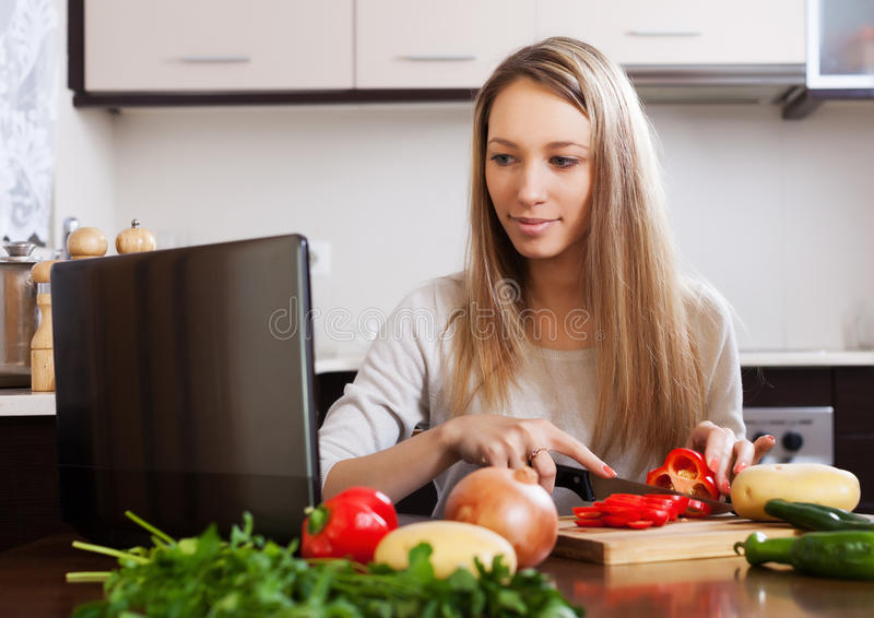 Vrouw het koken met laptop stock afbeelding
