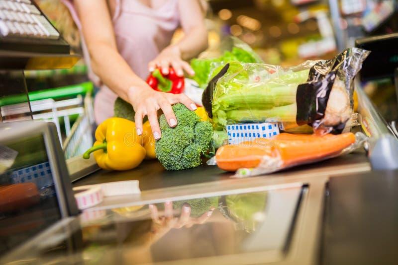 Vrouw het kopen voedsel bij de kruidenierswinkelopslag stock afbeelding