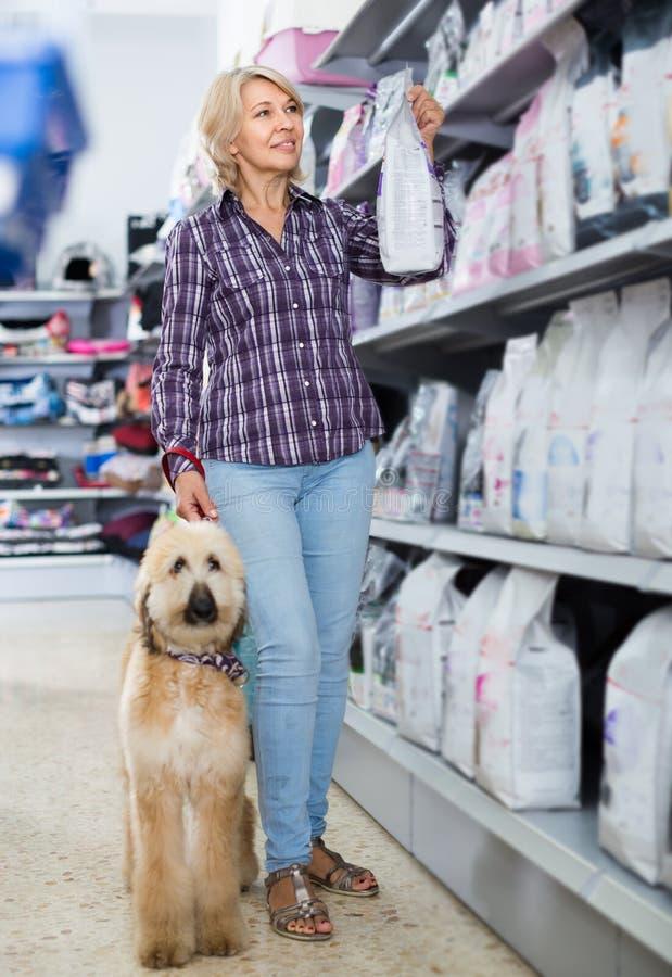 Vrouw het kopen voedsel voor huisdieren voor Afghaans Herderspuppy in winkel voor anim stock afbeelding