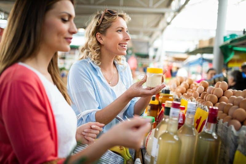 Vrouw het kopen vruchten en groenten bij lokale voedselmarkt stock afbeeldingen