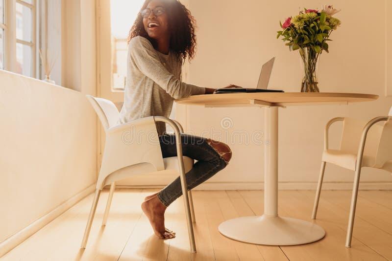 Vrouw het leiden zaken van huis met mobiele telefoon en laptop royalty-vrije stock afbeeldingen
