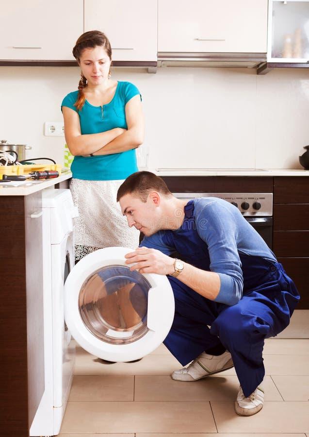 Vrouw het letten op als arbeider die wasmachine herstellen stock fotografie