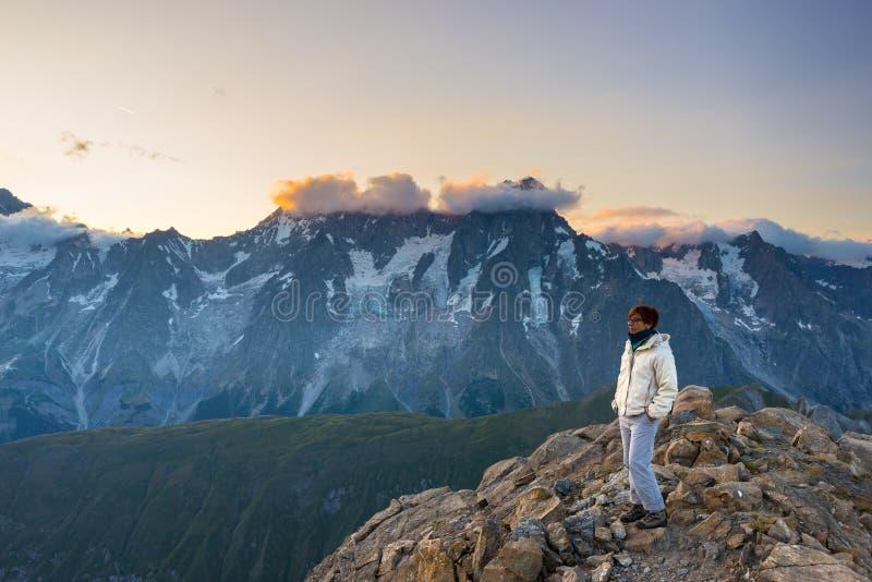 Vrouw het letten op overweldigende zonsopgang over valleien, randen en bergpieken Brede hoekmening van 3000 m in Valle D ` Aosta  royalty-vrije stock fotografie