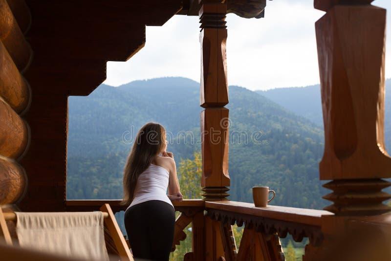 Vrouw het leunen op houten leuning en geniet en ontspant van mooie berg toneel Jong wijfje op terras die leunen stock foto's