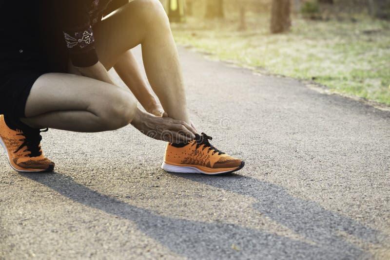 Vrouw het lopen op de weg krijgt ongeval op haar benen het beeld voor gezondheidsconcept is stock foto's