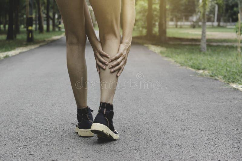 Vrouw het lopen op de weg krijgt ongeval voor haar benen het beeld voor gezondheidsconcept is stock fotografie