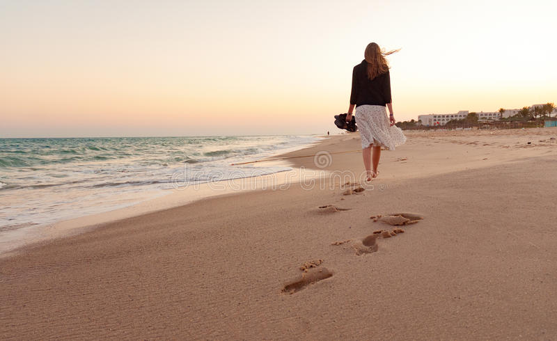 Vrouw het lopen strandzonsondergang stock afbeelding