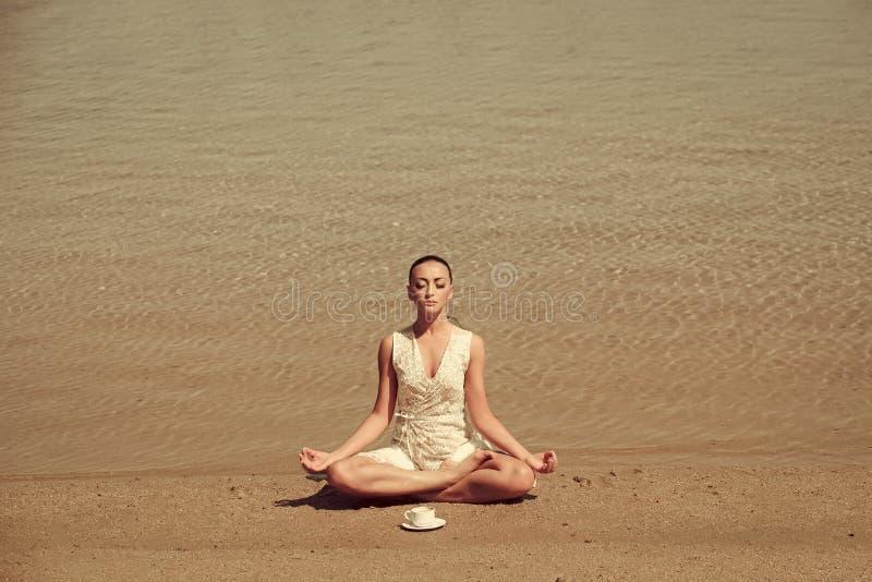 vrouw het mediteren in yoga stelt met koffiekop bij water royalty-vrije stock foto's
