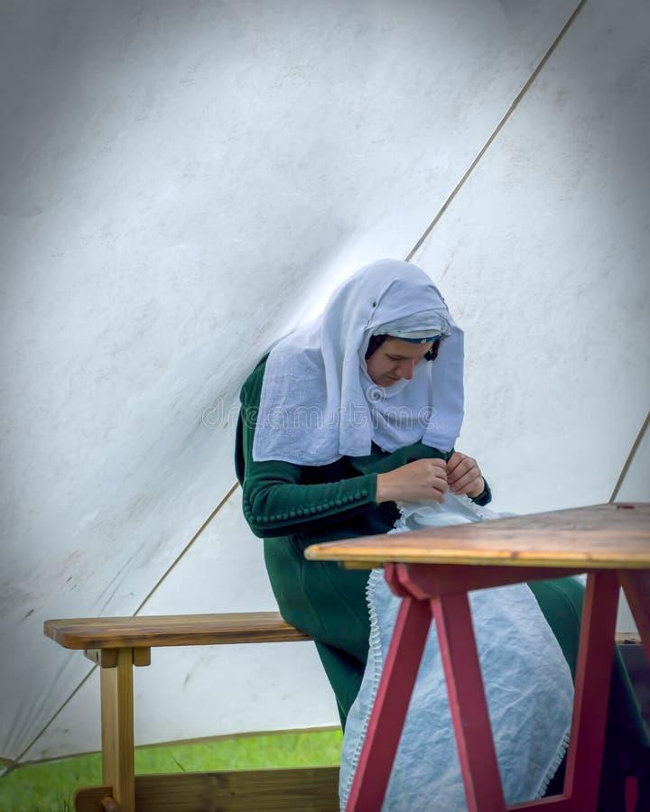 Vrouw in het middeleeuwse kostuum naaien stock afbeelding