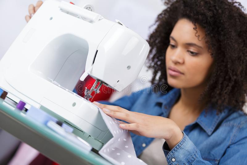 Vrouw het naaien op werkende plaats in manierworkshop stock foto