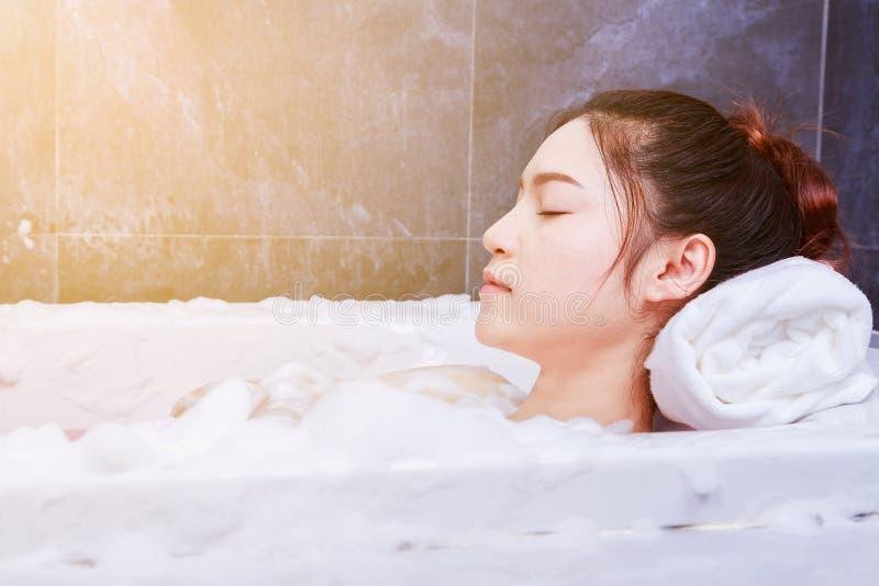 Vrouw het ontspannen in bathtube met ogen in badkamers worden gesloten die royalty-vrije stock fotografie