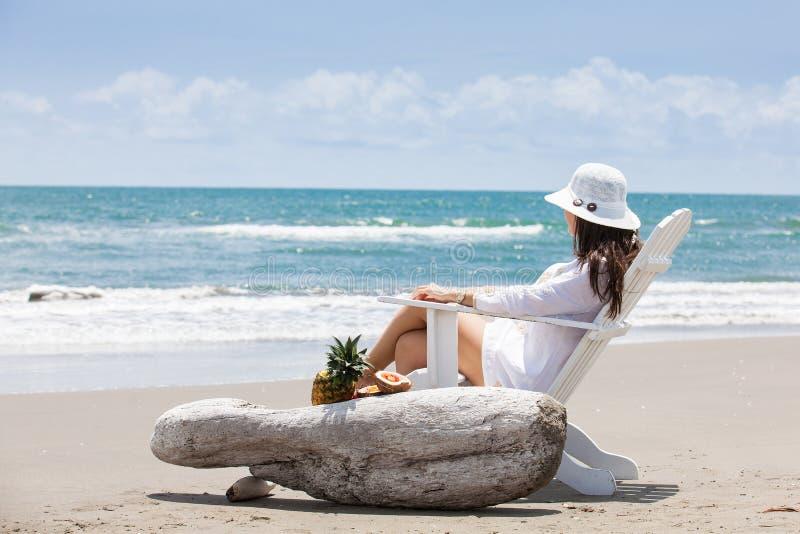 Vrouw het ontspannen bij een paradijselijk tropisch strand in een mooie zonnige dag royalty-vrije stock fotografie