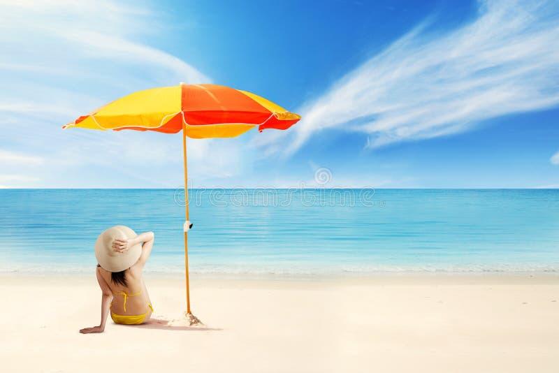 Vrouw het ontspannen bij kust onder paraplu royalty-vrije stock afbeelding