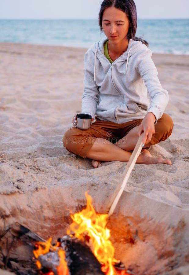Vrouw het ontspannen dichtbij een kampvuur op strand royalty-vrije stock fotografie