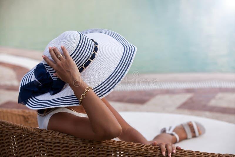 Vrouw het ontspannen dichtbij zwembad bij kuuroordtoevlucht royalty-vrije stock fotografie