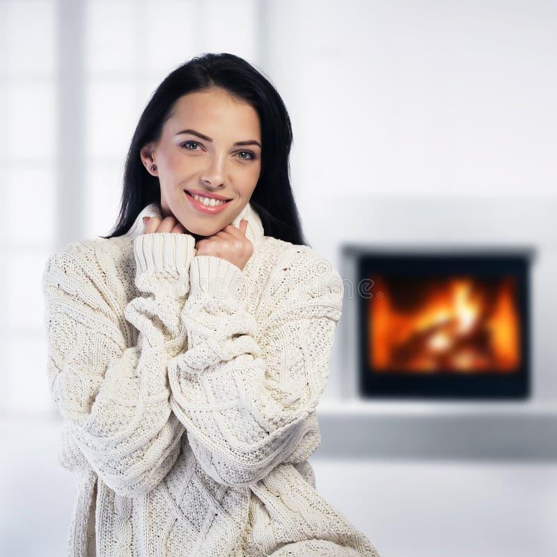 Vrouw het ontspannen door de open haard royalty-vrije stock foto