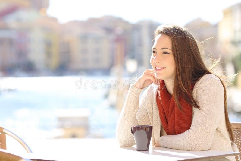 Vrouw het ontspannen in een koffiewinkel in een kuststad stock afbeeldingen