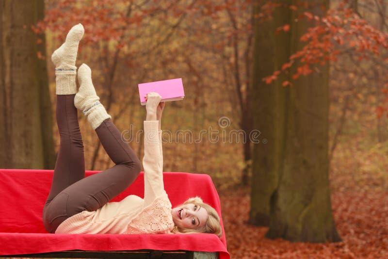 Vrouw het ontspannen in het boek van de het parklezing van de de herfstdaling royalty-vrije stock foto's