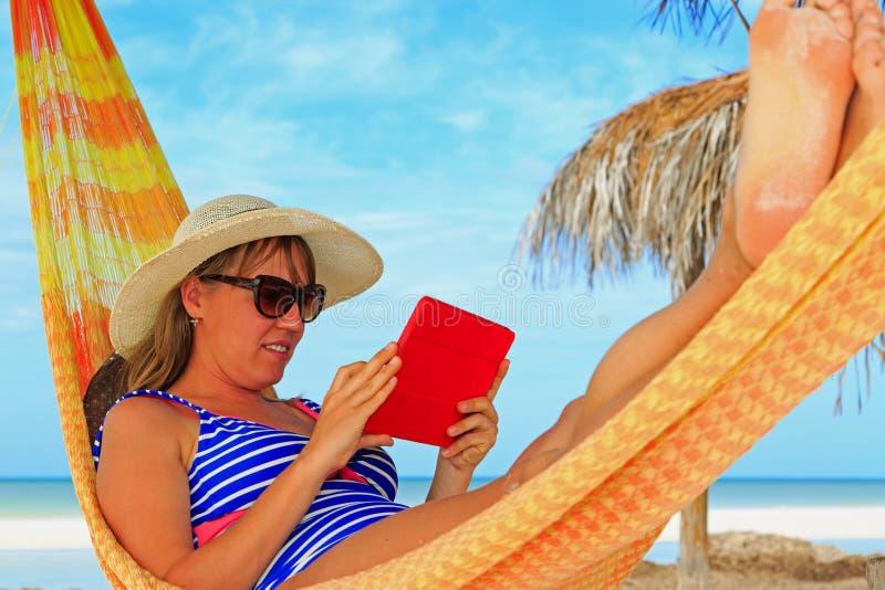 Vrouw het ontspannen in het stootkussen van de hammockwithaanraking bij het overzees stock foto's