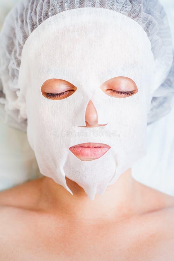 Vrouw het ontspannen in kuuroordsalon die wit gezichtsmasker toepassen royalty-vrije stock foto