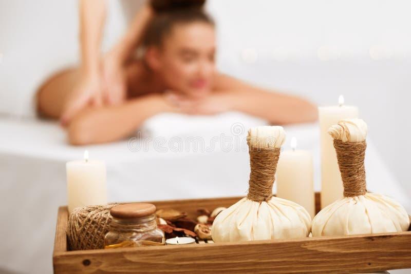 Vrouw het ontspannen in kuuroordsalon met kruidenzakken op houten dienblad royalty-vrije stock foto's