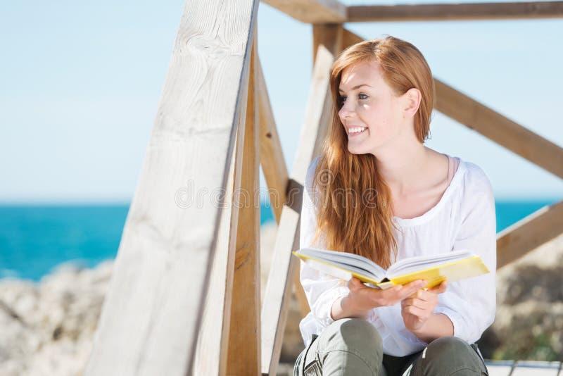 Vrouw het ontspannen met een boek bij het overzees royalty-vrije stock afbeeldingen