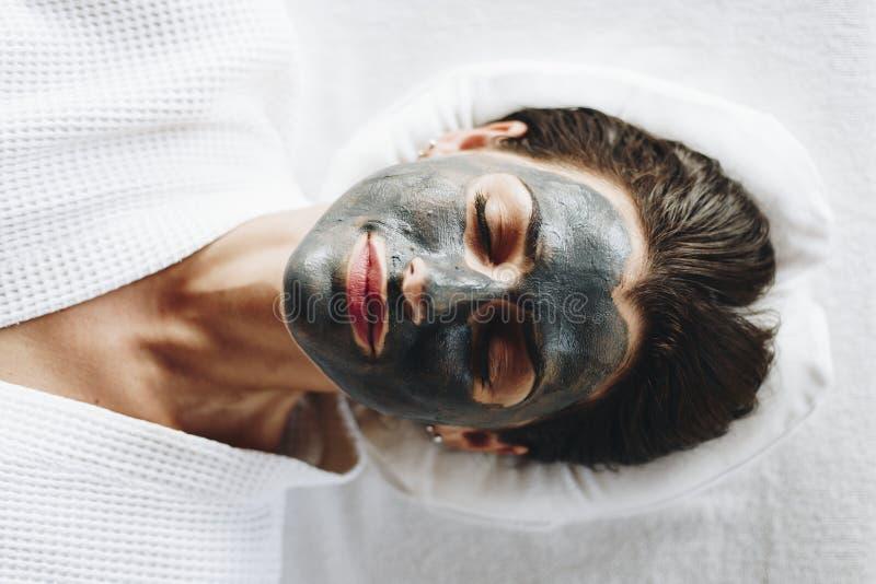 Vrouw het ontspannen met een houtskool gezichtsmasker stock fotografie
