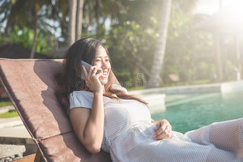 Vrouw het ontspannen naast de pool en het roepen gebruikend mobiele telefoon royalty-vrije stock afbeelding