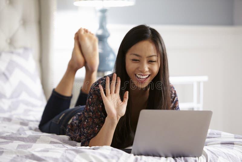 Vrouw het Ontspannen op Bed die Laptop Computer voor Videovraag met behulp van royalty-vrije stock fotografie
