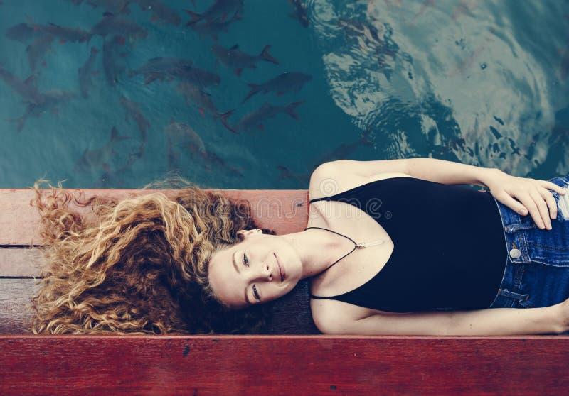 Vrouw het ontspannen op een houten pier royalty-vrije stock afbeeldingen