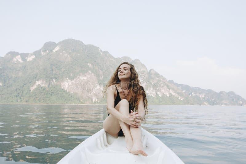 Vrouw het ontspannen op een kano bij een meer stock foto's