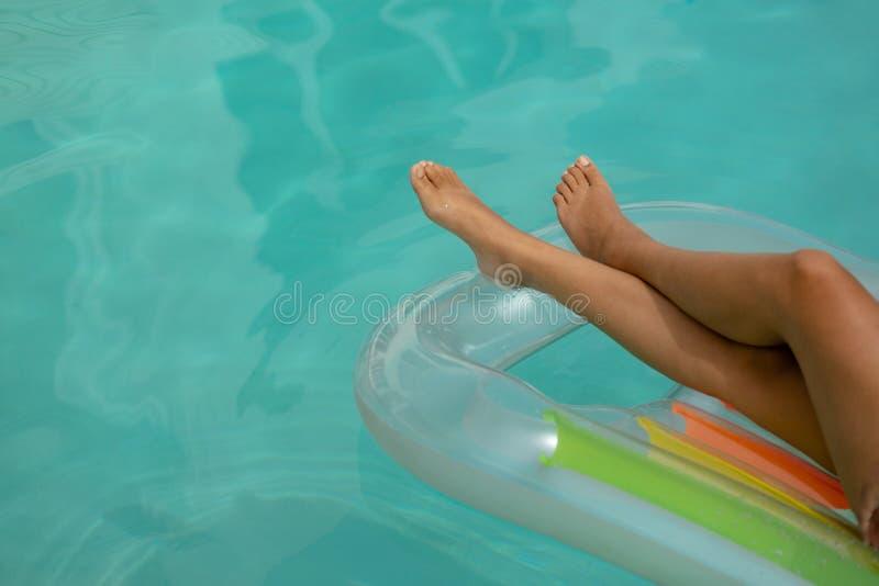 Vrouw het ontspannen op een opblaasbare buis in zwembad bij de binnenplaats van huis royalty-vrije stock afbeelding