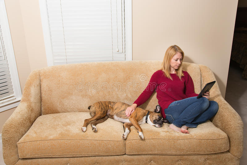 Vrouw het ontspannen op laag met haar hond en elektronisch apparaat stock foto